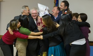 Podium members and friends surround Colin Holbrow, DTM in a group hug to honour his 30-year anniversary as a Toastmaster.